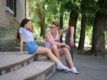 Ein schönes Mädchen und ein Gefährte mit einem longboard, das auf Steintreppe auf einem natürlichen unscharfen Hintergrund sitzt lizenzfreies stockfoto