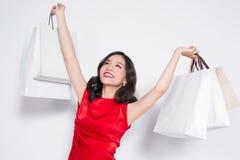 Ein schönes, modernes, luxuriöses Mädchen mit einem hellen Make-up in rote Kleider nahe bei den hellen Paketen nach dem Einkauf lizenzfreie stockbilder