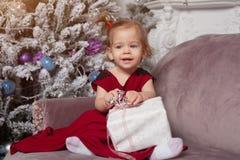 Ein schönes nettes kleines Mädchen, das in einem roten Kleid des eleganten Abends gekleidet wird, sitzt auf der Couch und öffnet  stockfoto