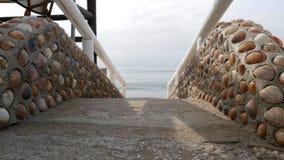 Ein schönes Treppenhaus gemacht von den Oberteilen, führend zu das Meer Lizenzfreie Stockbilder