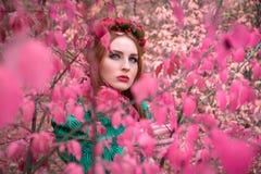 Ein schönes und fabelhaftes Mädchen in einem rosa Laub mit rotem Kranz Stockfotografie