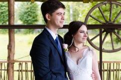 Ein schönes verheiratetes Paar in den Brautkleidern, werfend für ein Fotoschießen in einem belarussischen Dorf auf Grüner Hinterg Stockbilder
