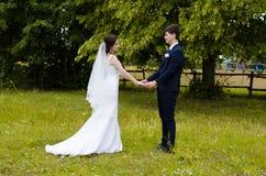 Ein schönes verheiratetes Paar in den Brautkleidern, werfend für ein Fotoschießen in einem belarussischen Dorf auf Grüner Hinterg Stockfotografie