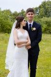 Ein schönes verheiratetes Paar in den Brautkleidern, werfend für ein Fotoschießen in einem belarussischen Dorf auf Grüner Hinterg Lizenzfreie Stockfotos