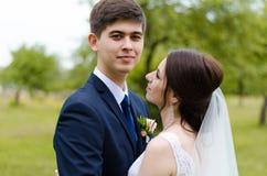 Ein schönes verheiratetes Paar in den Brautkleidern, werfend für ein Fotoschießen in einem belarussischen Dorf auf Grüner Hinterg Stockfoto