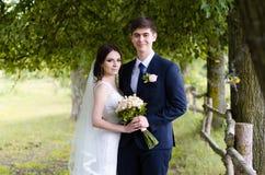 Ein schönes verheiratetes Paar in den Brautkleidern, werfend für ein Fotoschießen in einem belarussischen Dorf nahe dem Zaun, mit Lizenzfreies Stockfoto