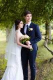Ein schönes verheiratetes Paar in den Brautkleidern, werfend für ein Fotoschießen in einem belarussischen Dorf nahe dem Zaun, mit Lizenzfreie Stockbilder