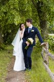 Ein schönes verheiratetes Paar in den Brautkleidern, werfend für ein Fotoschießen in einem belarussischen Dorf nahe dem Zaun, mit Stockbild