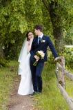 Ein schönes verheiratetes Paar in den Brautkleidern, werfend für ein Fotoschießen in einem belarussischen Dorf nahe dem Zaun, mit Lizenzfreie Stockfotos