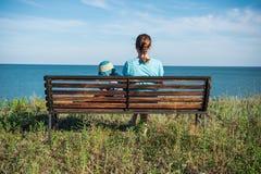 Ein Schönheit wuth Kind, das zum Meer vor der schönen Ozean- und Himmelansicht schaut Lizenzfreie Stockbilder