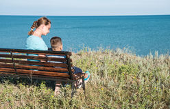 Ein Schönheit wuth Kind, das zum Meer vor der schönen Ozean- und Himmelansicht schaut Lizenzfreie Stockfotografie