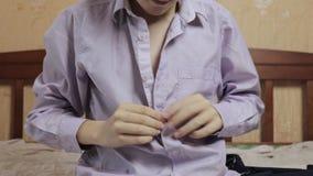 Ein Schüler, der Strickjacke und sein Hemd, ändernde Kleidung, Uniform aufknöpfen nach der Schule entfernt stock video footage