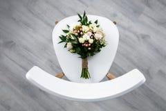 Ein sch?ner eleganter Blumenstrau? f?r die Braut liegt auf dem Stuhl lizenzfreie stockbilder