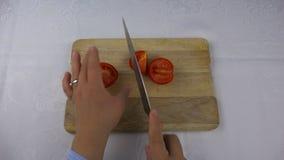 Ein scharfes Messer schneidet eine rote Tomate in vier Stücke stock video
