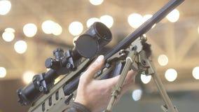 Ein Scharfschützegewehr in den Händen eines Mannes, ein optischer Anblick, ein Hintergrund, ein bokeh 60 fps stock video footage