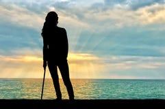 Ein Schattenbild einer Frau stützt sich mit einer Krücke Stockfotografie