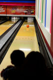 Ein Schattenbild einer Mutter und das Kind, das einen Ball aufpasst, gehen eine Bowlingbahn hinunter Stockfoto