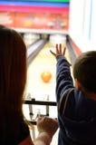Ein Schattenbild einer Mutter und das Kind, das einen Ball aufpasst, gehen eine Bowlingbahn hinunter Stockfotografie