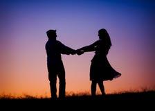 Ein Schattenbild eines jungen Paartanzens am sunse Lizenzfreie Stockfotografie