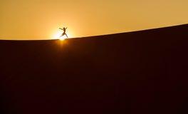 Ein Schattenbild eines Mädchens auf einem Wüste sandune bei Sonnenaufgang 6 Lizenzfreie Stockfotos