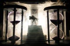 ein Schattenbild eines Mannes, der an zur Frau hält Rettungsretterkonzept Entweichen vom Feuer oder von der Gefahr Sanduhr, Feuer lizenzfreies stockfoto