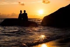 Ein Schattenbild eines Mannes und der Frau, die zusammen bei Sonnenuntergang auf einem Felsen im Ozean sitzen lizenzfreies stockfoto