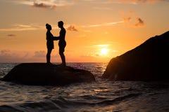 Ein Schattenbild eines Mannes und des Frauen-Händchenhaltens bei Sonnenuntergang auf einem Felsen im Ozean stockfotografie