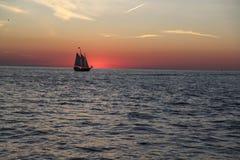 Ein Schiff auf dem Horizont bei Sonnenuntergang Stockfotografie