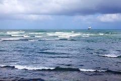 Ein Schiff im Abstand betritt den Seehafen in einem Seehafen, Meer und Wellen und ein blauer Hintergrund des bewölkten Himmels lizenzfreie stockfotos