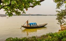 Ein Schiffer, der alte hölzerne Boote am See rudert, haben in Hooghly-Fluss Kolkata, sonniger Tag ein Bankkonto Stockfotografie