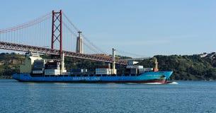 Ein Schiffsdurchlauf unter dem 25. von April Bridge, Lissabon, Portugal Lizenzfreie Stockbilder