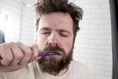 Ein schläfriger Mann mit seinen geschlossenen Augen, dem ungepflegten Haar und einem starken Bart putzt seine Zähne mit einer Zah stockfotos