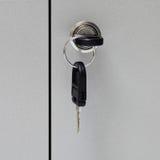 Ein Schlüssel im Schlüsselloch mit der Blockierung eines Schrankes Stockfotografie