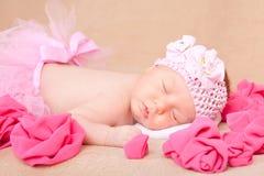 Ein schlafendes neugeborenes Baby, das ein rosa Stirnband und ein Ballettröckchen trägt lizenzfreie stockbilder