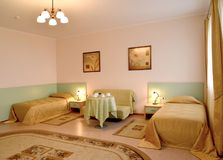 Ein Schlafzimmerinnenraum mit zwei Betten und ein Sofa in der klassischen Art Stockfoto
