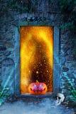 Ein schlecht lachender gespenstischer furchtsamer orange Kürbis mit glühenden Augen vor einer Kirchhoftür mit Feuer funkt nachts lizenzfreie stockfotografie