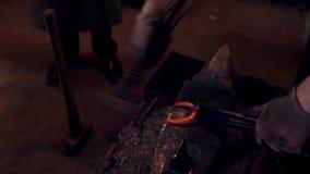 Ein Schmied, der ein Hufeisen mit einem Hammer auf Ambosse an der Werkstatt schmiedet Mann, der mit heißem rotem Metall arbeitet stock video footage