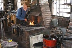 Ein Schmied, der schwarzes Metall in einem historischen Shop 100 Jähriger (Schmiede) bearbeitet Schmiedeim Galena Lizenzfreies Stockfoto