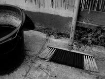 Ein schmutziger Besen und ein Eimer lizenzfreie stockbilder