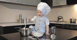 Ein schmutziger kleiner Koch in einer kulinarischen Kappe sitzt auf einer Tabelle und Spielen mit Mehl stock video footage