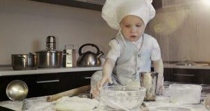 Ein schmutziger kleiner Koch spielt mit Mehl und Teig auf dem Tisch in der Küche stock footage