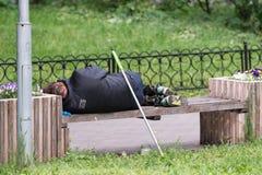 Ein schmutziger obdachloser Mann, der in einer schwarzen Jacke auf einer Straßenbank schläft lizenzfreies stockfoto