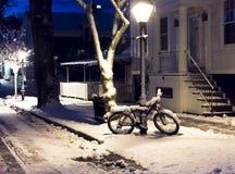Ein Schnee bedeckte Fahrrad nachts unter einem Laternenpfahl stockbild