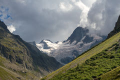 Ein Schnee bedeckter Berg ist unter drohenden Wolken sonnenbeschien Lizenzfreie Stockfotografie