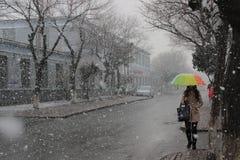 Ein Schneetag in JLU Ein junges Mädchen ist unter einem bunten Regenschirm lizenzfreie stockfotos