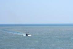 Ein Schnellboot, das Wasserwellenkurve macht Stockfotografie