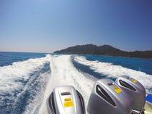 Ein Schnellboot mit drei Maschinen, die zurück zu Ufer segeln, das die weiße vermischte Welle machte lizenzfreies stockbild