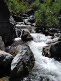 Ein schneller flüssiger Nebenfluss angeschmiegt zwischen den Bergen lizenzfreie stockfotografie