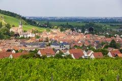 Ein schönes französisches Dorf im Elsass mit Kirche unter Weinbergen. Lizenzfreies Stockbild