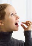 Ein schönes Mädchen, das eine Tablette nimmt Stockfoto